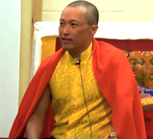 Sakyong teaching in yellow shirt, orange robe