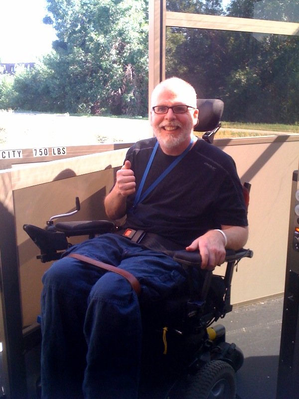 Image of Larry Seidl, one of our webmasters, in his wheelchair on our lift elevator.